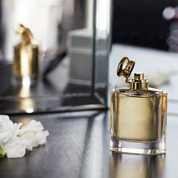 Frasco do perfume em frente a um espelho